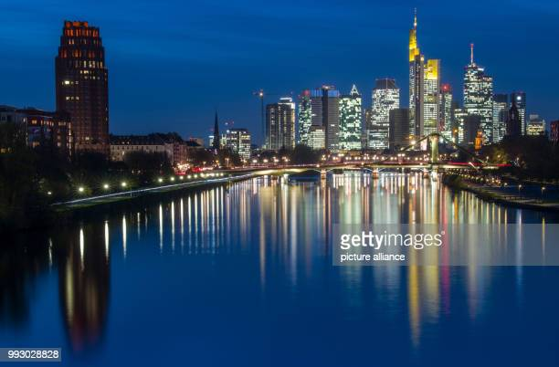 Dpatop - The banking towers of the Frankfurt skyline can be seen in the last light of day and are mirrored in the Main river inFrankfurt am...