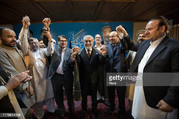 """Dr Abdullah receives the support of Mirwais, son of Afghanistan's last king from 1933 to 1973 Zaher Shah, by giving him the """"chapan"""" or """"king's hate""""..."""