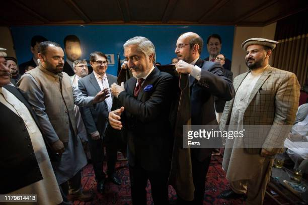 """Dr Abdullah receives the support of Mirwais, son of Afghanistan's last king from 1933 to 1973 Zaher Shah, by giving him the """"chapan"""" or """"""""king's..."""