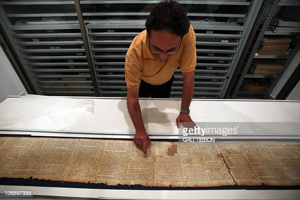 Dr. Adolfo Roitman, curator of the Dead Sea Scrolls and head of the Shrine of the Book points at the original Isaiah scroll found in Qumaran caves in...