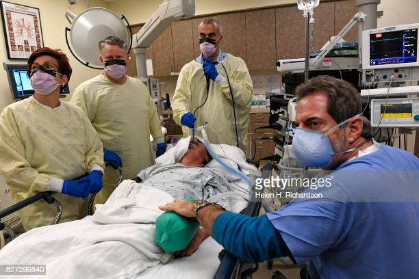 Dr Akrum AlZubaidi DO middle performs a bronchoscopy on patient Orlando Carrasco with the help of his team from left to right Ana Stefan RN Mike...