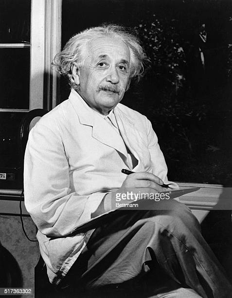 Dr Albert Einstein is shown seated inside by the window writing