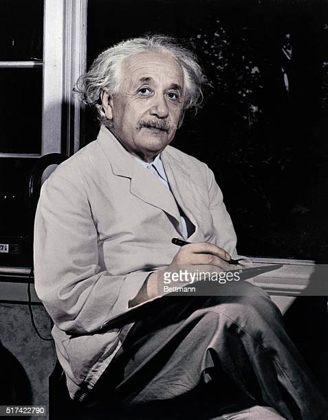 Dr. Albert Einstein is shown seated inside by the window, writing.