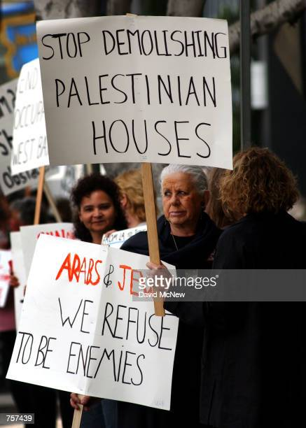 """Dr. Alice Powell, who is Jewish, holds a sign reading """"Arabs and Jews, we refuse to be enemies"""" outside the Israeli Consulate in protest of current..."""