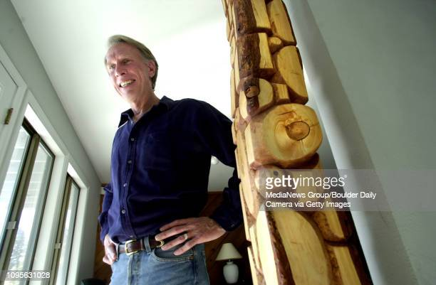 Dr Allen Saville poses with one of his art pieces that he created using fallen wood on his property in Boulder