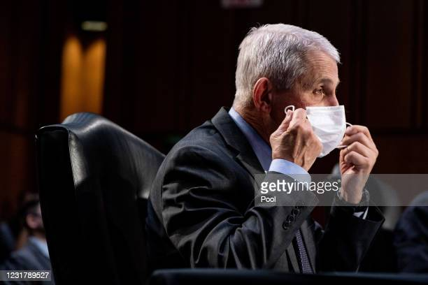 Dr. Anthony Fauci, Director at the National Institute Of Allergy and Infectious Diseases, takes off his face mask during a hearing, with the Senate...