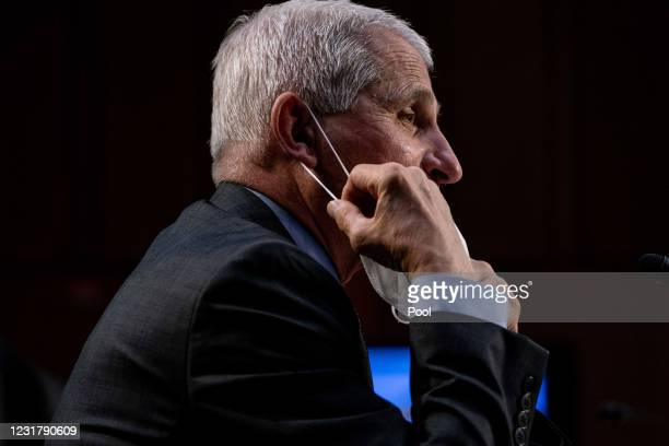Dr. Anthony Fauci, Director at the National Institute Of Allergy and Infectious Diseases, takes his face mask off during a hearing with the Senate...