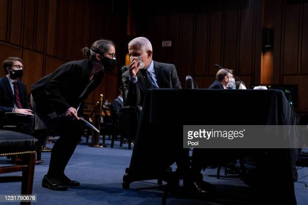 Dr. Anthony Fauci, Director at the National Institute Of Allergy and Infectious Diseases, speaks to one of his staff members during a hearing with...