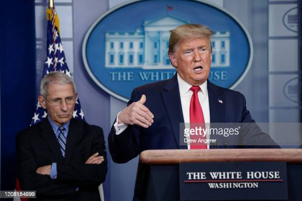 Dr Anthony Fauci director of the National Institute of Allergy and Infectious Diseases listens to US President Donald Trump speak during a briefing...