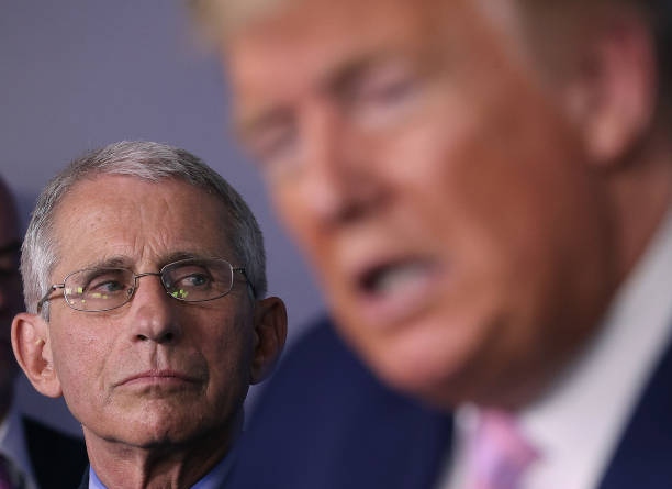 Dr. Anthony Fauci director of the National Institute of Allergy and Infectious Diseases, listens to U.S. President Donald Trump speak from the press...