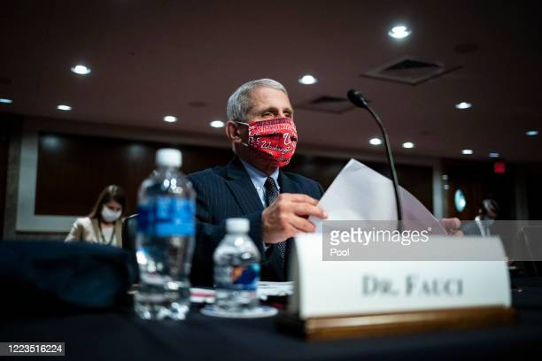 Dr. Anthony Fauci, director of the National Institute of Allergy and Infectious Diseases, wears a Washington Nationals protective mask while arriving...