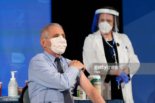 Dr. Anthony Fauci, director of the National Institute of Allergy and Infectious Diseases, speaks as he holds up his sleeve in preparation to receive...