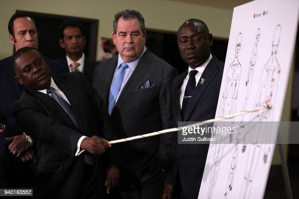 Dr Bennet Omalu points to a chart as he discusses results of his autopsy of Stephon Clark as attorneys Brian Panish and Ben Crump look on during a...