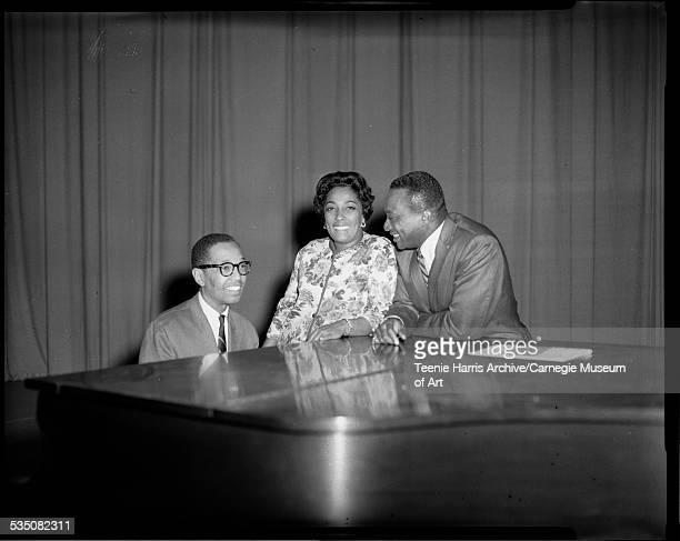 Dr Billy Taylor at piano with Carmen McRae and Walt Harper standing beside him in front of plain curtain Pittsburgh Pennsylvania 1965