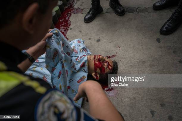 Dr Chiu holds up a sheet over a victim of gang violence in the busy suburb of Zone 18 on October 21 2017 in Guatemala City Guatemala Guatemala City...