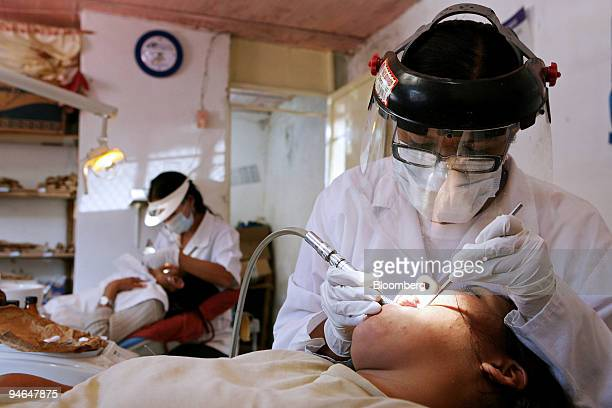 Dr Dalia Lizano right a dentist from Cuba checks a patient's teeth at the Bolivarian Medical Mission in Caracas Venezuela on Nov 29 2007