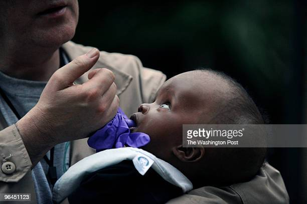 Dr Dan Purdim from the MO1 DMAT holds a baby with possible congenital hydrocephalus which was transported by Navy helicopter to a field hospital with...
