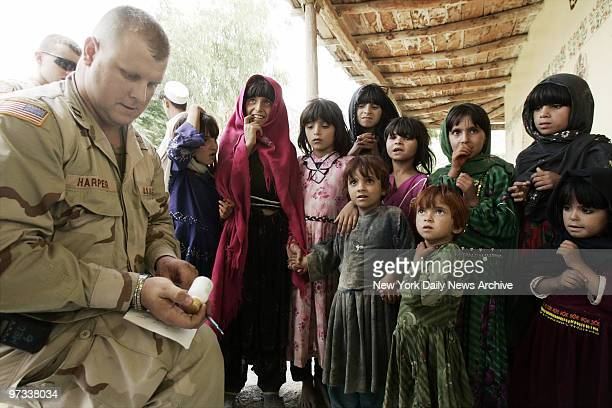 Dr. David Harper, of the Army's 82nd Airborne Division, distributes medicine to waiting Afghan girls at a makeshift clinic set up in an area known...