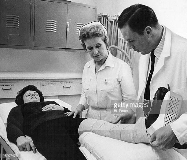 NOV 23 1965 NOV 27 1965 DEC 1 1965 Dr E Harold Evenson an orthopedic surgeon examines the 'broken leg' of a skier Miss Lee Ann Cliff with the help of...