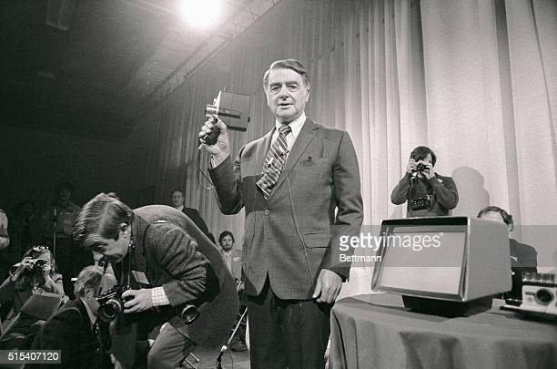 Dr Edwin K Land founder and chairman of Polaroid Corporation holds aloft his new 'instant' home movie camera and the projector r which he introduced...