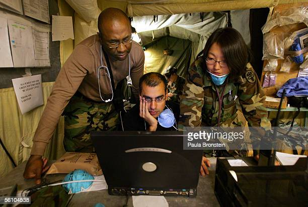 Dr Eric McDonald with 212 MASH US Air Force with the 435th medical Group Dr Fareed Sheikh and Dr Mary Choi study the computer for medical information...