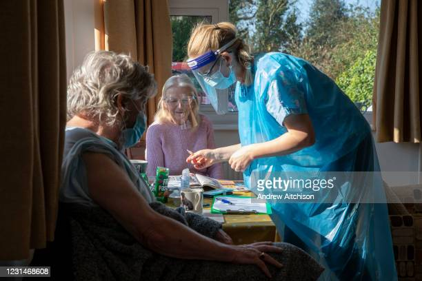 Dr Fordham of the Channel Health Alliance prepares a syringe of the AstraZeneca COVID-19 vaccination before administering it to a housebound patient...