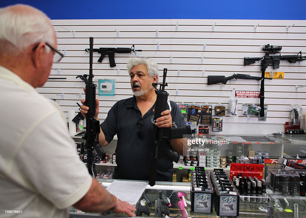 Dr. Gary Lampert (R), a co-owner of the National Armory gun store, helps Richard Fuller as he looks to buy a National Armory AR-15 Battle Entry Assault Rifle on January 16, 2013 in Pompano Beach, Florida. President Barack Obama today in Washington, DC announced a broad range of gun initiatives that his administration thinks will help curb gun violence.