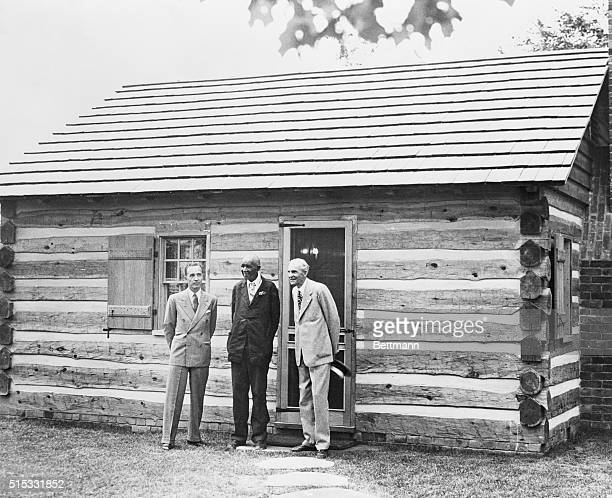 Dr George Washington Carver eminent Negro scientist is pictured with Edsel Ford left and Henry Ford right in front of the modernly equipped log cabin...
