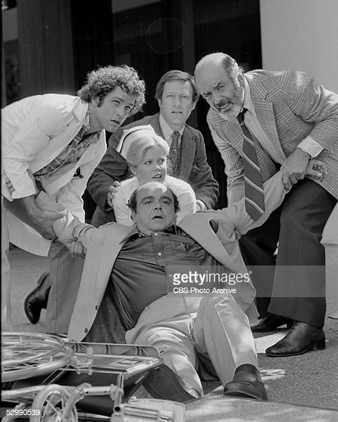 Dr Gonzo Gates Nurse Gloria 'Ripples' Brancusi and Dr Trapper John help to lift up a fallen patient as Arnold Slocum looks on in a scene from the tv...