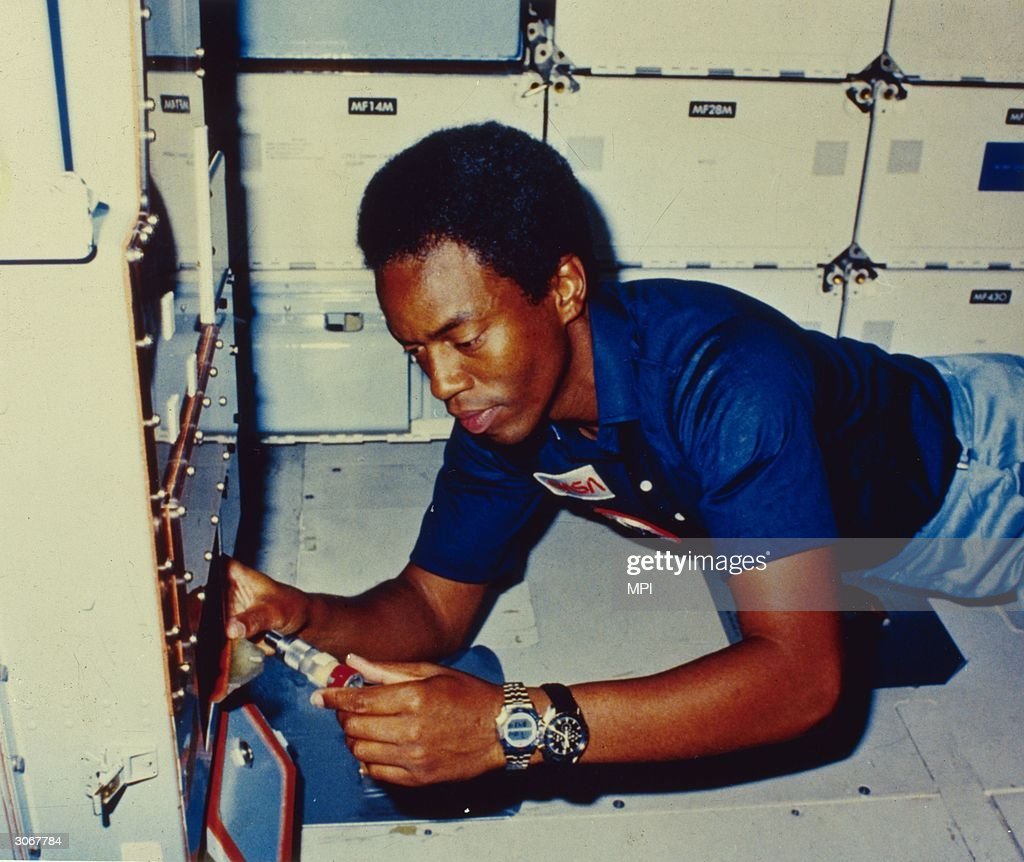 Dr Guion S Bluford Jnr, a mission specialist on STS-8, the third flight of the Orbiter Challenger checks out the sample pump on the continuous flow electrophoresis system (CFES) on the mid-deck. CFES is an experiment designed to separate biological materials according to their surface electrical charge as they pass through an electric field.