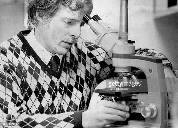 1982 JAN 17 1982 Dr H Peter Chase clinical director looks at pancreas cells on microscope slide
