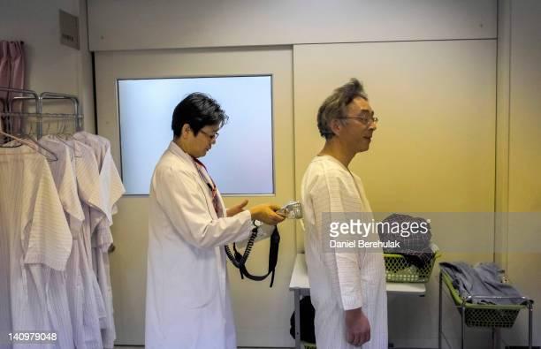 Dr Hanai Tatsui prepares patient Ichiji Ishizawa to be screened for radiation during a whole body radiation check at the Minamisoma City General...