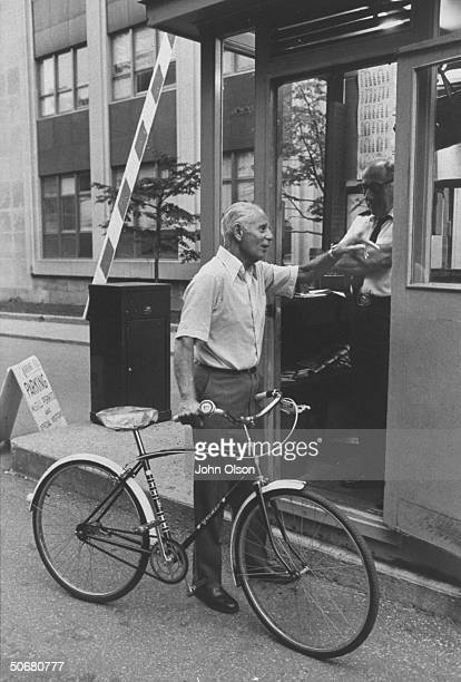 Dr Hans Selye head of Institute of Exprimmental Research and Surgery talking to a guard while riding his bicycle