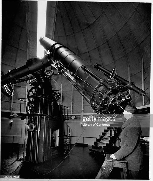 Dr Harry E Burton principal astronomer at the United States Naval Observatory in Washington DC looks through a telescope to follow the wandering moon...