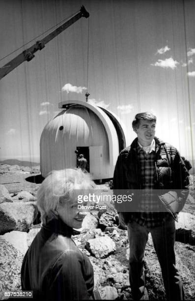 Dr Janet Rountree Lesh DU Dr Charles Lillie CU stand by as workmen prepare to place the 1400Pound declination axle on telescope mount at the Mt Evans...