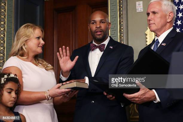 Dr Jerome Adams places his hand on a bible held by his wife Lacy Adams as he is sworn in as US Surgeon General by Vice President Mike Pence in the...