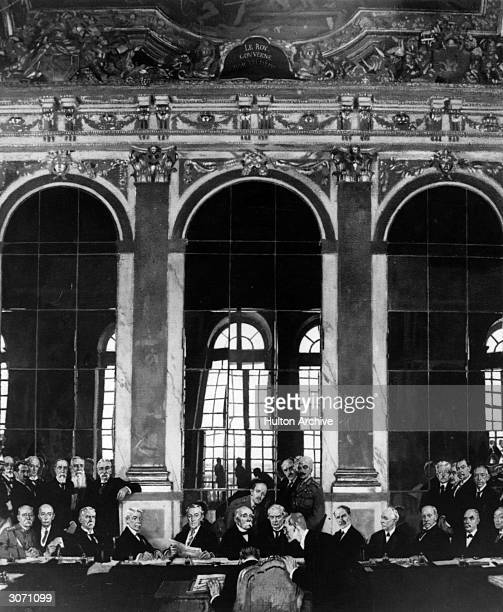 Dr Johannes Bell of Germany signing the peace declaration at Versailles. German Foreign Minister Hermann Muller is leaning over him, also present are...