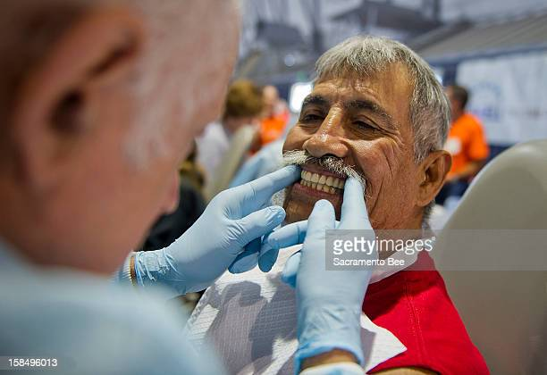 Dr John Nardone left checks new dentures on Mike Martinez of Modesto who lost all of his top teeth three months ago Dr Lawrence Wallace of Carmel...