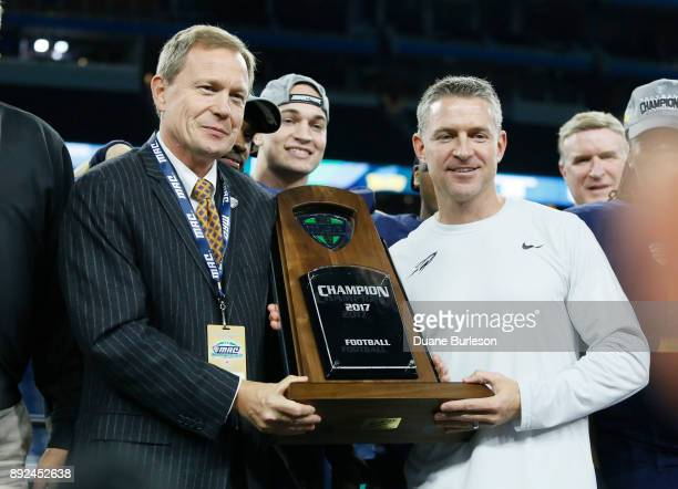 Dr Jon Steinbrecher commissioner of the MidAmerican Conference presents the MAC Championship trophy to head coach Jason Candle of the Toledo Rockets...
