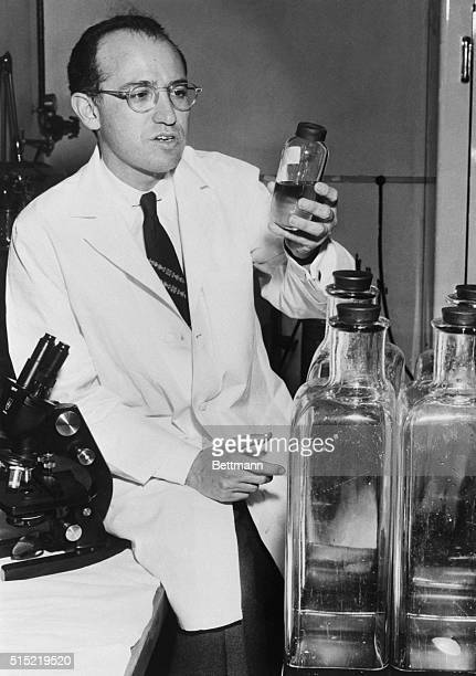 Dr. Jonas E. Salk checks samples of virus-laden fluid used in the production of his vaccine, as he returns to his University of Pittsburgh...