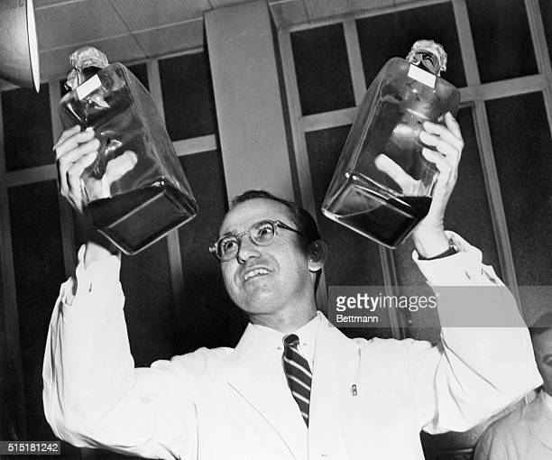 Dr. Jonas Salk displays his polio vaccine which he developed in a University of Pittsburgh laboratory.