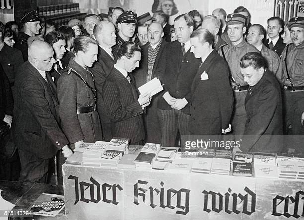 Dr. Joseph Goebbels, Minister of Propaganda, is shown glancing through one of the books during his recent visit to the Book Show in the Europa...