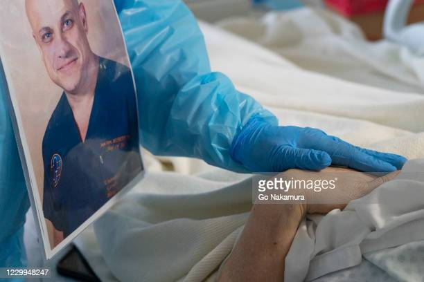 Dr. Joseph Varon places his hand on a patient's hand in the COVID-19 intensive care unit at the United Memorial Medical Center on December 4, 2020 in...