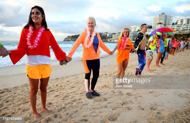 Dr Kerryn Phelps links arms with surfers on the Bondi Beach shoreline on March 22 2019 in Sydney Australia Surfers gather to celebrate five years of...