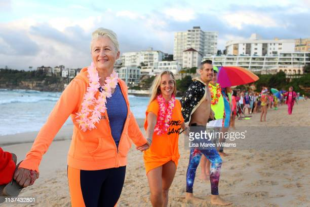 Dr Kerryn Phelps links hands with surfers in solidarity with OneWave at sunrise on Bondi Beach on March 22 2019 in Sydney Australia Surfers gather to...