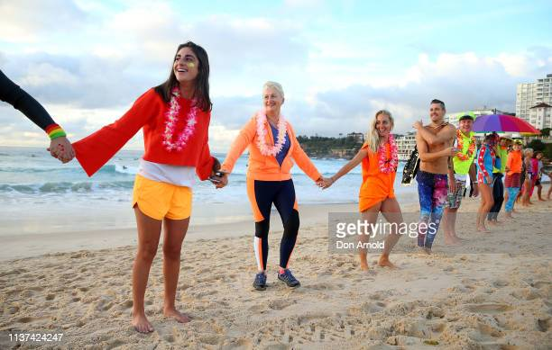 Dr Kerryn Phelps links hands with surfers on the Bondi Beach shoreline on March 22 2019 in Sydney Australia Surfers gather to celebrate five years of...