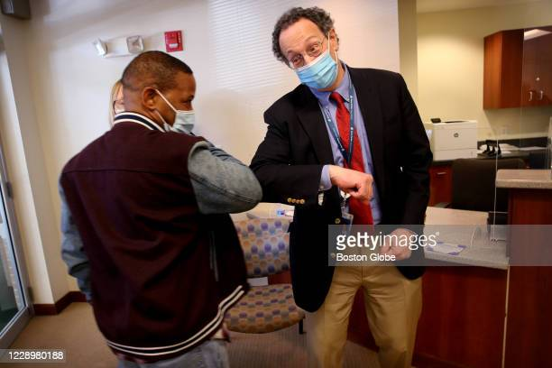 Dr. Lindsey Baden, right, bumps elbows with COVID-19 vaccine trial participant Anthony Shivers after speaking with the media at Brigham and Women's...