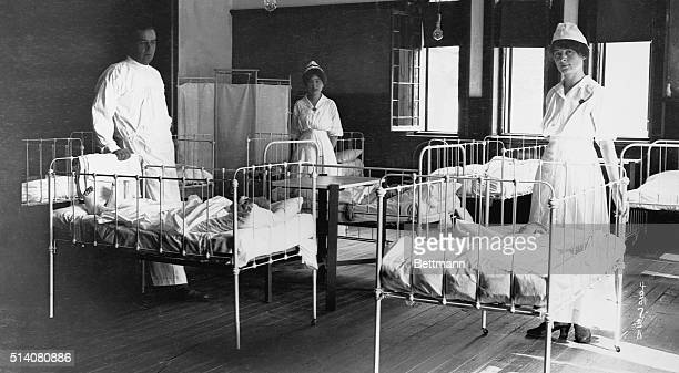 Dr. L.M. Sims and nurses Mrs. Callahan and Mrs. McCormick in a hospital ward with victims of the infantile paralysis epidemic of 1916 in Beacon, NY.