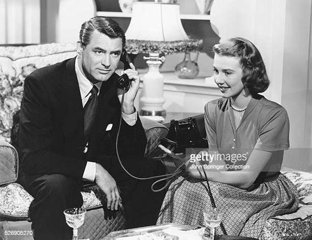 Dr Madison Brown talks on the phone as Anabel Sims sits beside him in a scene from the 1948 comedy Every Girl Should Be Married