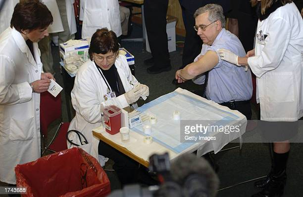 Dr Marcia Trape administers a smallpox vaccination to Dr Richard Garibaldi the head of the University of Connecticut Health Center January 24 2003 in...